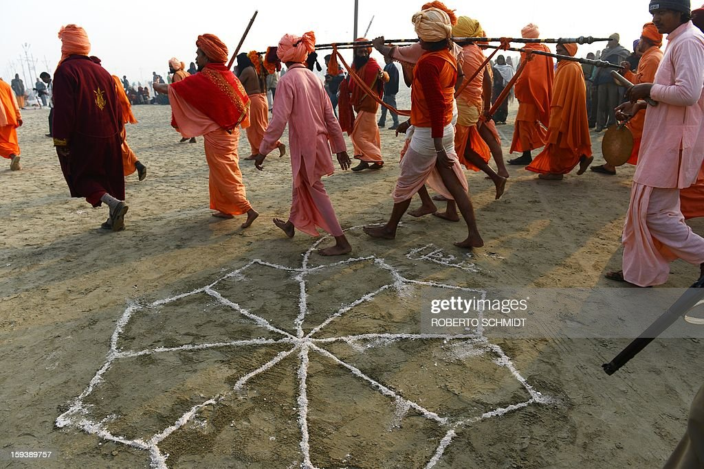 Sadhus, or holy men, walk past a sand decoration after performing a ritual prayer at the water's edge at the Sangham or confluence of the Yamuna and Ganges river during a short ritual at the Kumbh Mela celebration in Allahabad on January 13, 2013. The Kumbh Mela in northern India, starting January 13 and stretching over 55 days, attracts ash-covered holy men who run into the frigid waters, a smattering of international celebrities, as well as millions upon millions of ordinary Indians to Allahabad, at the confluence of the rivers Yamuna and Ganges.
