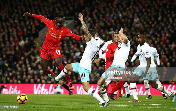 Sadio Mane of Liverpool is challenged by Manuel Lanzini of West Ham during the Premier League match between Liverpool and West Ham United at Anfield...