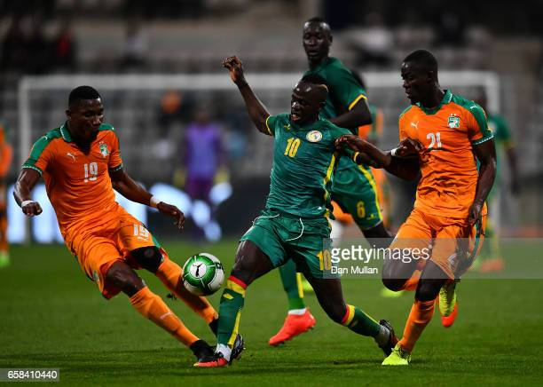 Sadio Mane of Senegal holds off Simon Deli and Eric Bailly of the Ivory Coast during the International Friendly match between the Ivory Coast and...
