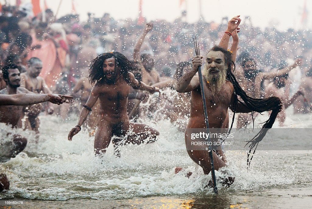 Saduhs or holy men run into the waters of the Sangham or the confluence of the the Yamuna and Ganges rivers during the Kumbh Mela in Allahabad on January 14, 2013. Hundreds of thousands of Hindu pilgrims led by naked, ash-covered holy men streamed into the sacred river Ganges on Monday at the start of the world's biggest religious festival. The Kumbh Mela in the Indian town of Allahabad will see up to 100 million worshippers gather over the next 55 days to take a ritual bath in the holy waters, believed to cleanse sins and bestow blessings. Before daybreak on Monday, a day chosen by astrologers as auspicious, hundreds of gurus, some brandishing swords and tridents, ran into the swirling and freezing waters for the first bath, signalling the start of events.