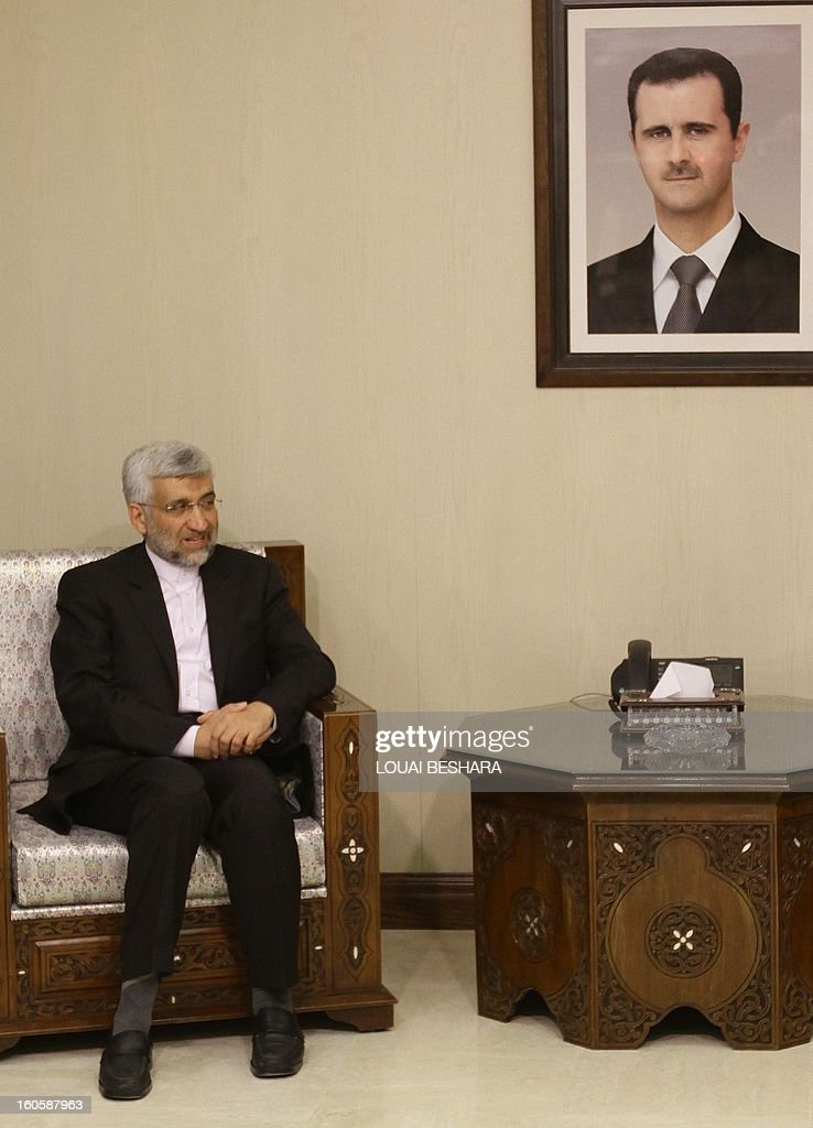 Saeed Jalili, who heads the Iranian Supreme National Security Council, sits near a portrait of Syrian President Bashar al-Assad as he meets Syrian Foreign Minister during a meeting on February 3, 2013 in Damascus. 'We will give all our support so that Syria remains firm and able to face all the arrogant (Western) conspiracies,' said Saeed Jalili on February 2.