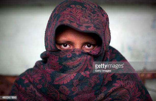 Safa covers her face with her shawl while she sits for a photo January 22 2014 in the Shamli District of Uttar Pradesh India According to her on...
