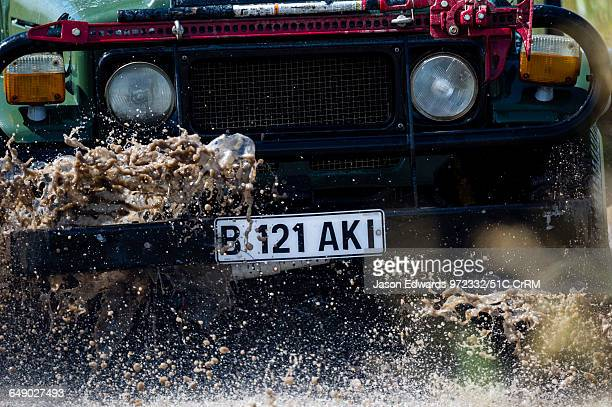 A safari 4wd splashes through the mud of a waterhole