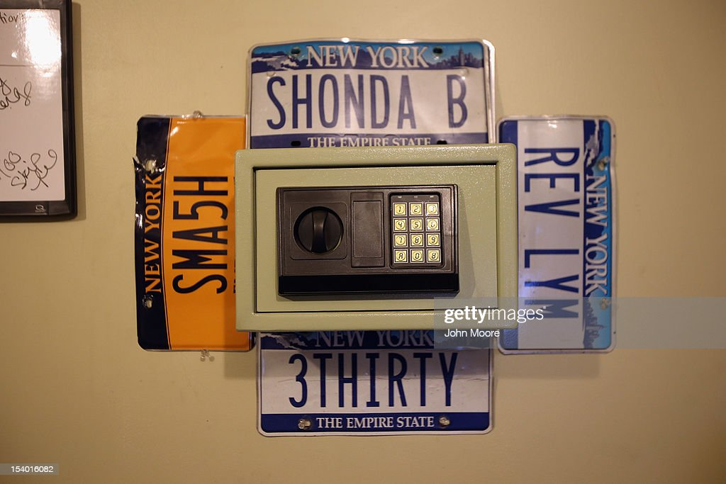A safe hangs, surrounded by confiscated license plates, on the wall of Advanced Recovery of New York on October 11, 2012 in Syracuse, New York. Recovery agents, knows as 'repo men' work day and night locating and towing vehicles legally repossessed by banks and loan agencies, after the owners stop making payments.