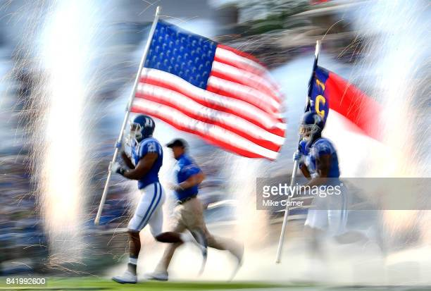 Safety Alonzo Saxton II of the Duke Blue Devils carries the United States flag onto the field before the Blue Devils' game against the North Carolina...