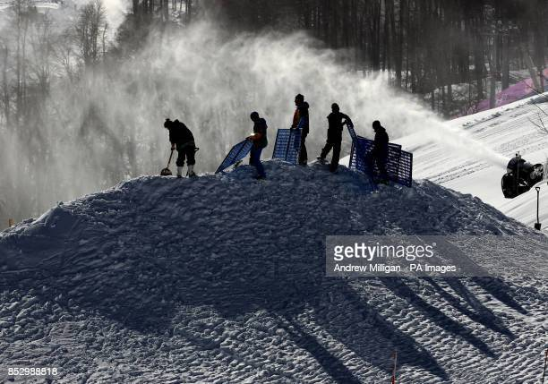 Safety barriers are put up as a snow blower is seen at the slopestyle course at the Rosa Khutor Extreme Park Sochi Russia