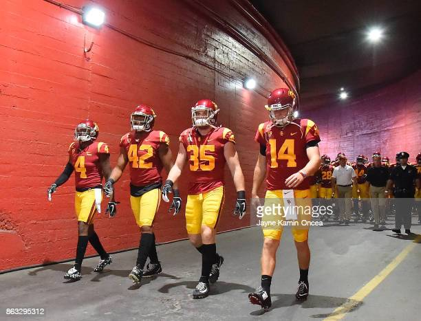 Safety Chris Hawkins linebacker Uchenna Nwosu linebacker Cameron Smith and quarterback Sam Darnold of the USC Trojans lead the team down the tunnel...