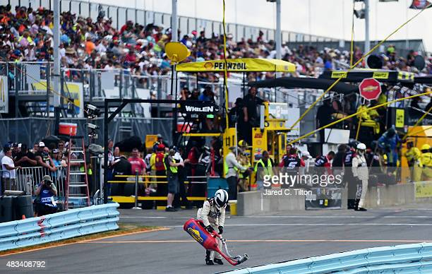 A safety crew member removes a fuel canister from pit road after Joey Logano driver of the Snapon Ford left his pit box with the cannister still...