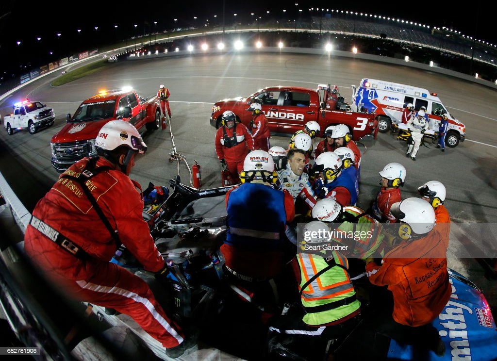 Safety crew workers place Aric Almirola, driver of the #43 Smithfield Ford, on a stretcher after cutting off the roof of his car after a crash during the Monster Energy NASCAR Cup Series Go Bowling 400 at Kansas Speedway on May 13, 2017 in Kansas City, Kansas.