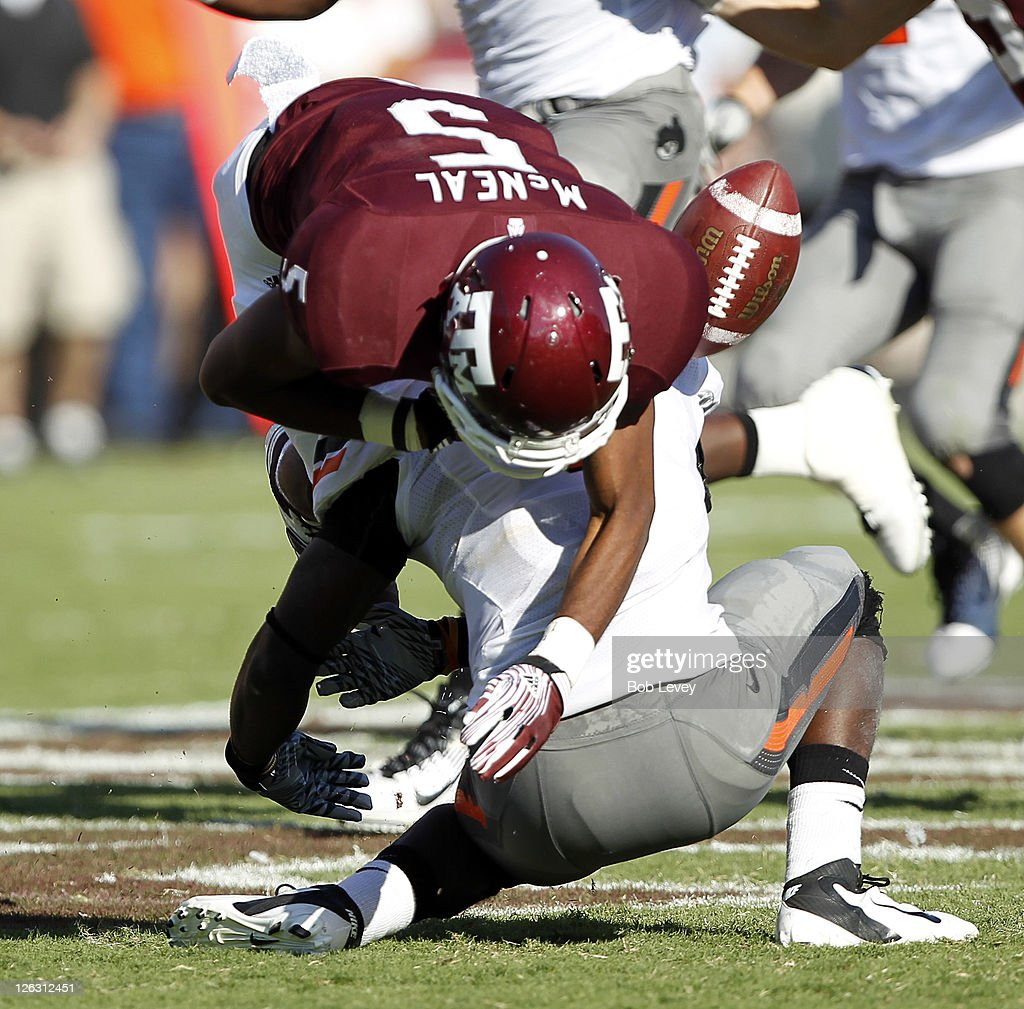 Safety Daytawion Lowe #8 of the Oklahoma State Cowboys lays his helmet on the ball causing wide receiver Kenric McNeil #5 of the Texas A&M Aggies to fumble the ball in the third quarter at Kyle Field on September 24, 2011 in College Station, Texas. Oklahoma State won 30-29.