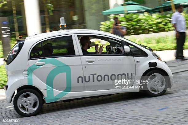 A safety driver sits in a moving driverless car during a public trial run in Singapore on September 23 2016 Southeast Asia's leading ridehailing firm...