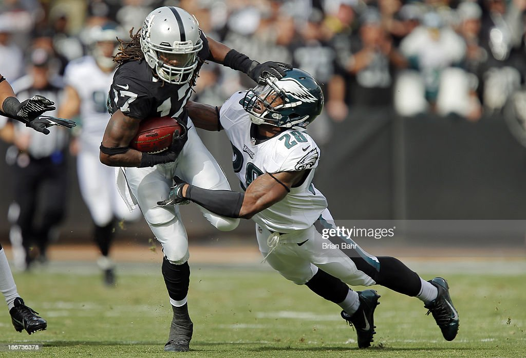 Safety Earl Wolff #28 of the Philadelphia Eagles brings down wide receiver Denarius Moore #17 of the Oakland Raiders on a 27-yard catch on the third play from scrimmage in the first quarter on November 3, 2013 at O.co Coliseum in Oakland, California. The Eagles won 49-20.