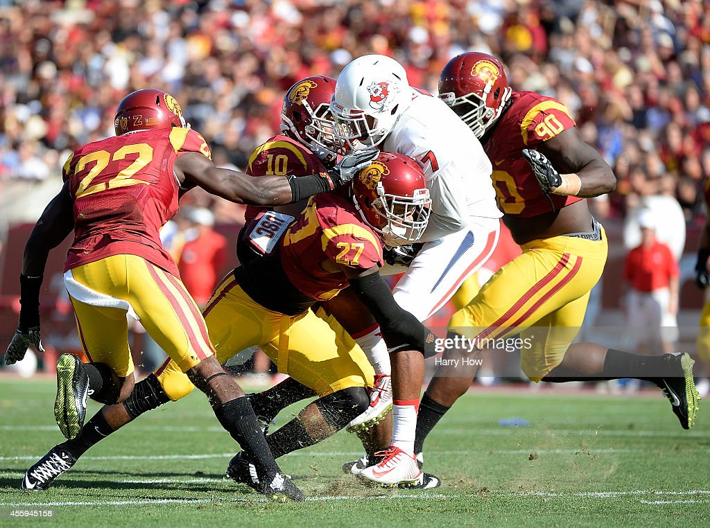 Safety Gerald Bowman #27 of the USC Trojans tackles wide receiver Aaron Peck #7 of the Fresno State Bulldogs at Los Angeles Memorial Coliseum on August 30, 2014 in Los Angeles, California.