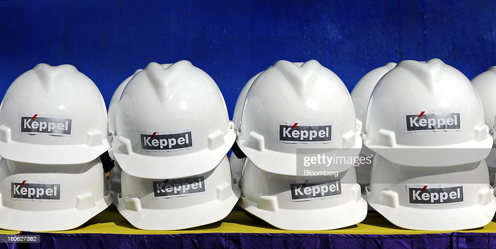 Safety hats featuring the Keppel Corp. logo stand on a table during a rig-naming ceremony at the Keppel FELS shipyard in Singapore, on Saturday, Feb. 2, 2013. Keppel Corp.'s FELS unit received a combined $1.5 million bonus for completing the construction of two drilling rigs ahead of time, the company said in a statement. Photographer: Munshi Ahmed/Bloomberg via Getty Images