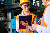 Portrait of young woman making notes on clipboard while talking to senior worker in  modern workshop,  both wearing hardhats and reflective jackets
