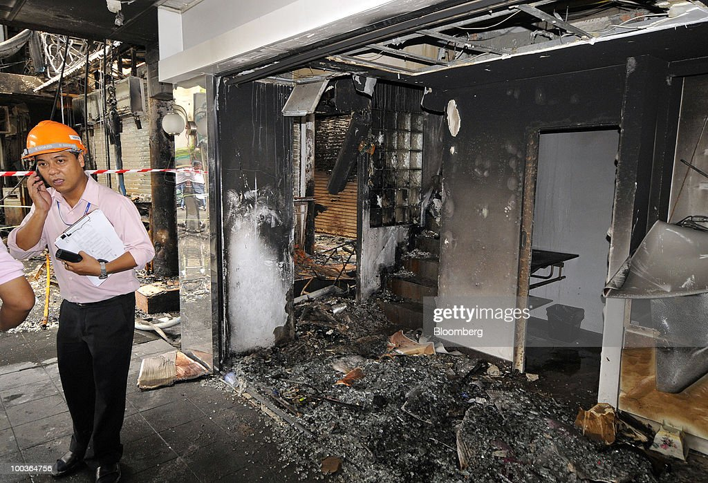 A safety inspector speaks on his mobile as he inspects the burned remains of shops in the Siam Square shopping area in Bangkok, Thailand, on Monday, May 24, 2010. Efforts to clean up the city's commercial district gathered pace after the area was torched by rioting anti-government protesters. Photographer: Udo Weitz/Bloomberg via Getty Images