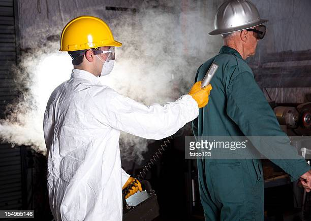 Safety inspector with Geiger counter testing worker