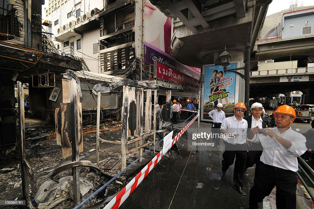 Safety inspectors assess the damage to a bank and phone booth in the Siam Square shopping area in Bangkok, Thailand, on Monday, May 24, 2010. Efforts to clean up the city's commercial district gathered pace after the area was torched by rioting anti-government protesters. Photographer: Udo Weitz/Bloomberg via Getty Images