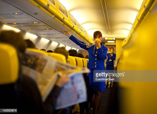 Safety instructions shown by a stewardess for Passengers boarding for departure of a RyanAir flight to Alicante Spain at Allgaeu Airport on February...