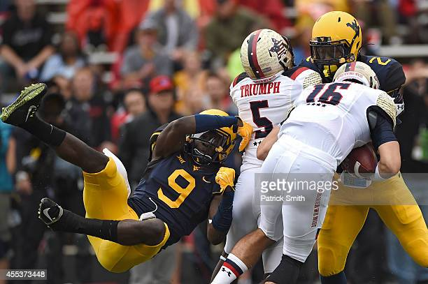 Safety KJ Dillon of the West Virginia Mountaineers tries to pull down quarterback CJ Brown of the Maryland Terrapins in the first quarter during an...