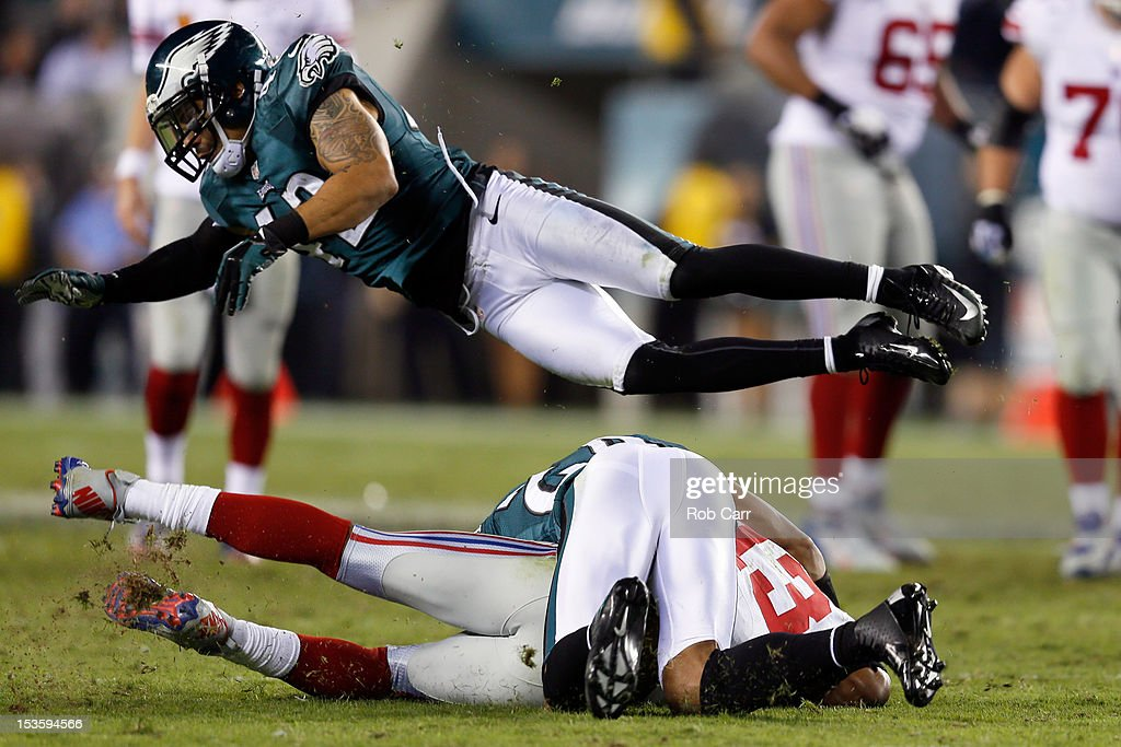 Safety Kurt Coleman #42 of the Philadelphia Eagles dives over wide receiver Ramses Barden #13 of the New York Giants at Lincoln Financial Field on September 30, 2012 in Philadelphia, Pennsylvania.