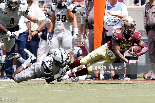 Safety Larenzo Mathis of the Charleston Southern Buccaneers tackled Wide Receiver Travis Rudolph of the Florida State Seminoles during the game at...