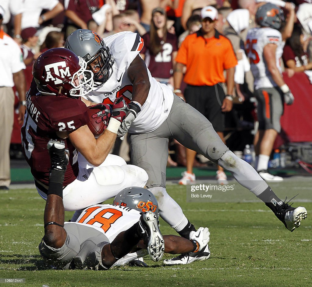 Safety Markell Martin #10 of the Oklahoma State Cowboys lays a hard hit on running back Ryan Swope #25 of the Texas A&M Aggies as Devin Hedgepeth #18 hits him low at Kyle Field on September 24, 2011 in College Station, Texas. Martin was called for a pesonal foul on the play. Oklahoma State won 30-29.