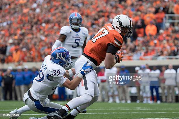 Safety Michael Glatczak of the Kansas Jayhawks tackles tight end Blake Jarwin of the Oklahoma State Cowboys during the first quarter of a NCAA...