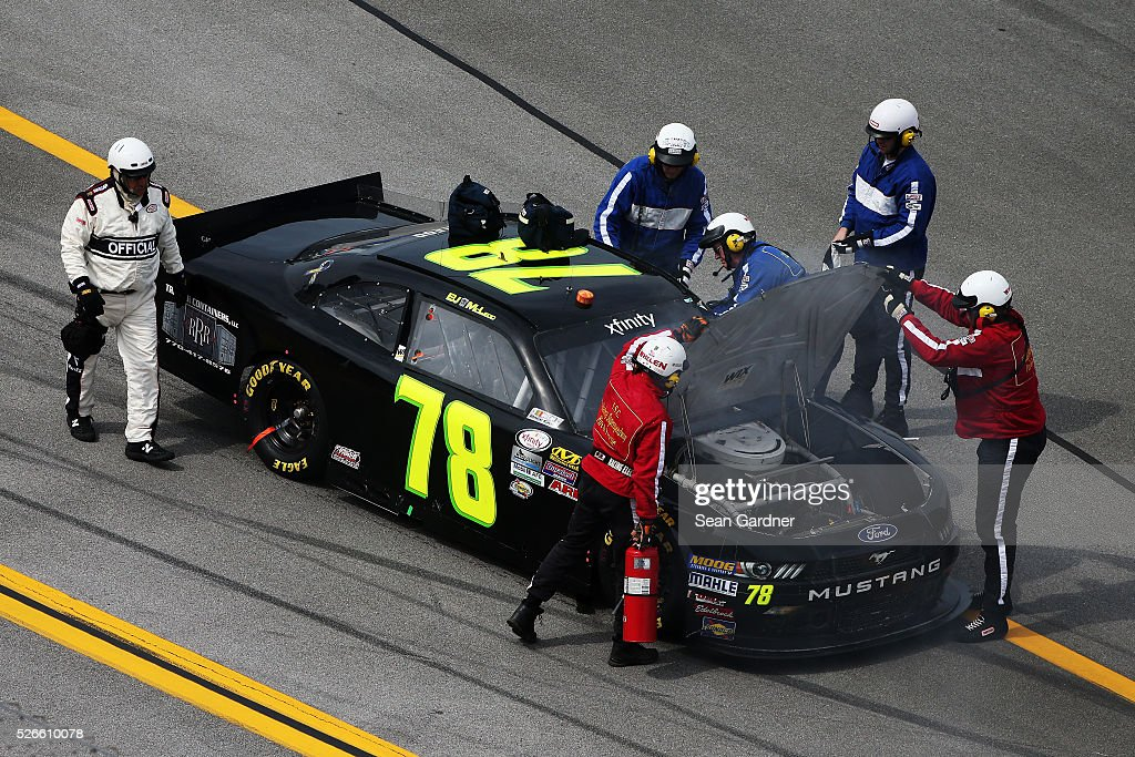 Safety officials assist BJ McLeod, driver of the #78 Triple R Containers LLC Ford, after an on track incident during the NASCAR XFINITY Series Sparks Energy 300 at Talladega Superspeedway on April 30, 2016 in Talladega, Alabama.