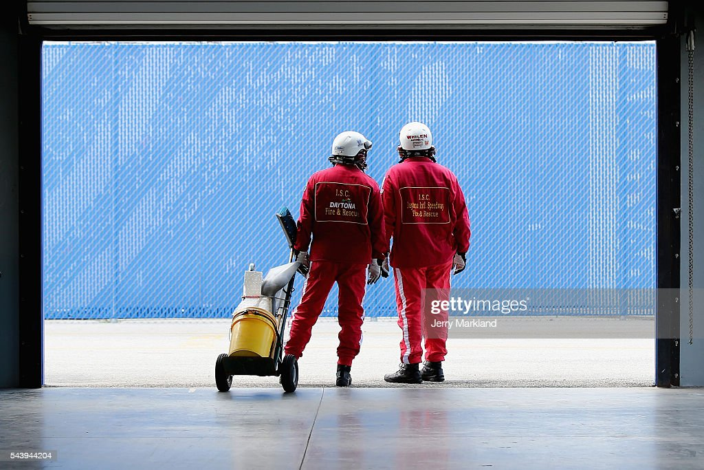 Safety officials look on from the garage area during practice for the NASCAR XFINITY Series Subway Firecracker 250 at Daytona International Speedway on June 30, 2016 in Daytona Beach, Florida.