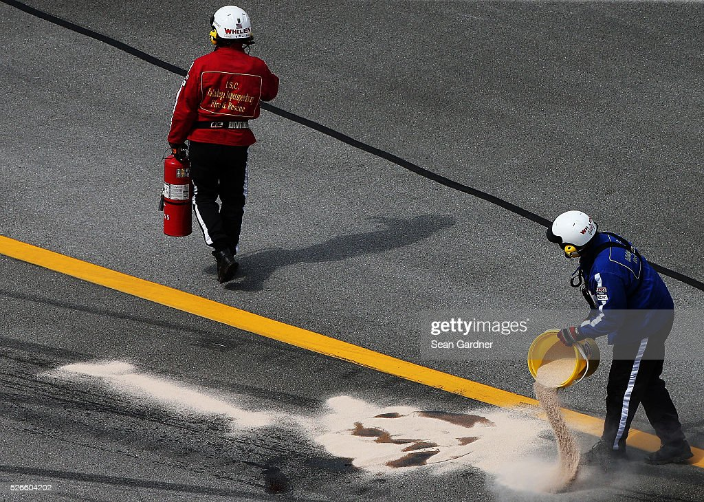 Safety officials work to dry oil on the track during the NASCAR XFINITY Series Sparks Energy 300 at Talladega Superspeedway on April 30, 2016 in Talladega, Alabama.