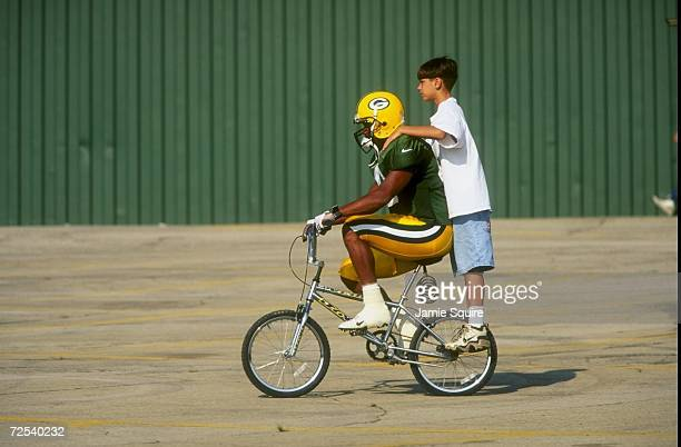 Safety Pat Terrell of the Green Bay Packers gives a fan a ride on a bike during the Packers Training Camp at Lambeau Field in Green Bay Wisconsin