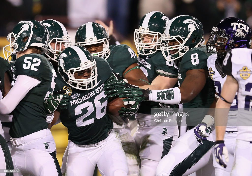 Safety RJ Williamson #26 of the Michigan State Spartans celebrates with teammates after fumble recovery during the fourth quarter of the Buffalo Wild Wings Bowl against the TCU Horned Frogs at Sun Devil Stadium on December 29, 2012 in Tempe, Arizona. The Spartans defeated the Horned Frogs 17-16.