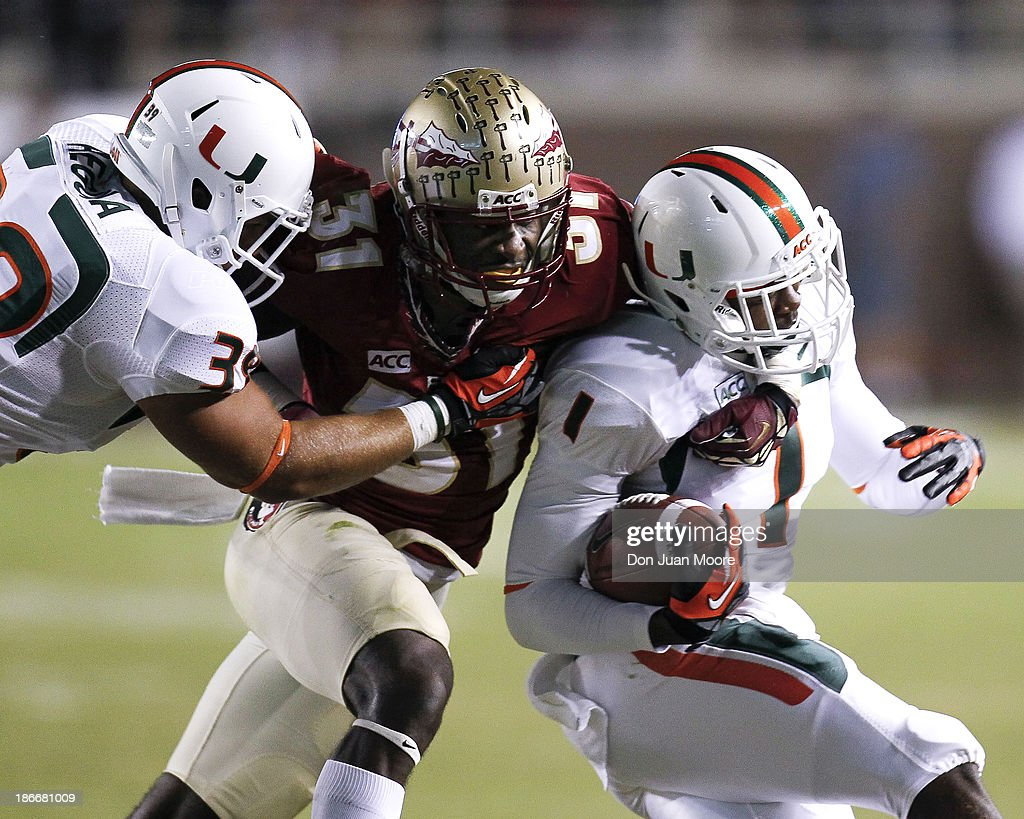 Safety Terrance Brooks #31 of the Florida State Seminoles makes a one handed tackle against Wide Receiver Allen Hurns #1 of the Miami Hurricanes as Linebacker Ronald Regula #39 trys to block during the game at Doak Campbell Stadium on Bobby Bowden Field on November 2, 2013 in Tallahassee, Florida. 3rd ranked Florida State defeated 7th ranked Miami 41 to 14.