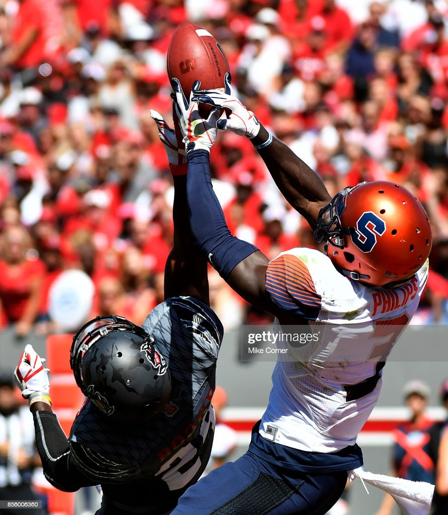 Safety Tim Kidd-Glass #34 of the North Carolina State Wolfpack breaks up a pass intended for wide receiver Ervin Philips #3 of the Syracuse Orange in the end zone during the football game at Carter Finley Stadium on September 30, 2017 in Raleigh, North Carolina.