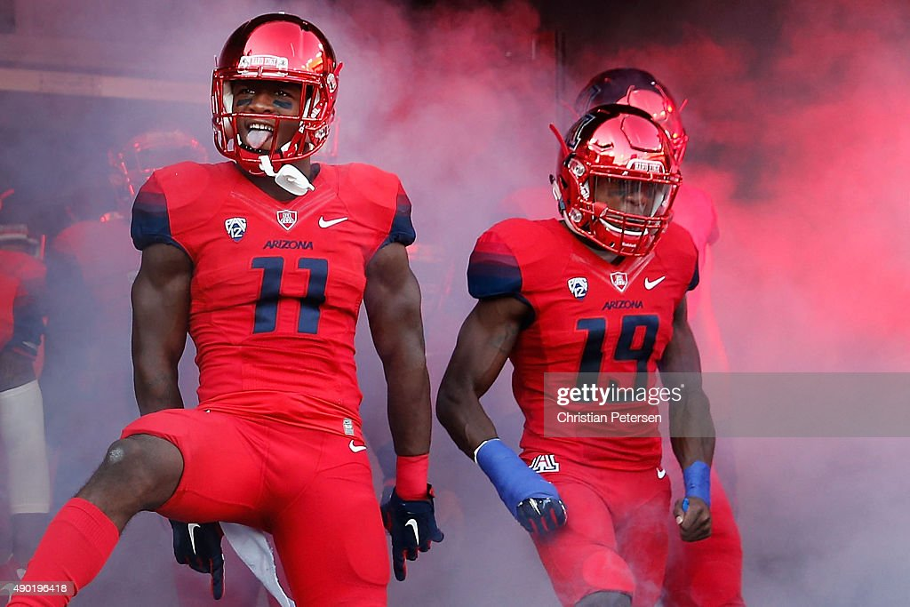 Safety Will Parks #11 and cornerback DaVonte' Neal #19 of the Arizona Wildcats react as they are introduced to the college football game against the UCLA Bruins at Arizona Stadium on September 26, 2015 in Tucson, Arizona.