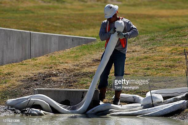 A safety worker places absorbent booms to collect toxic runoff as Waxahachie fire fighters battle a massive fire Magnablend chemical processing plant...
