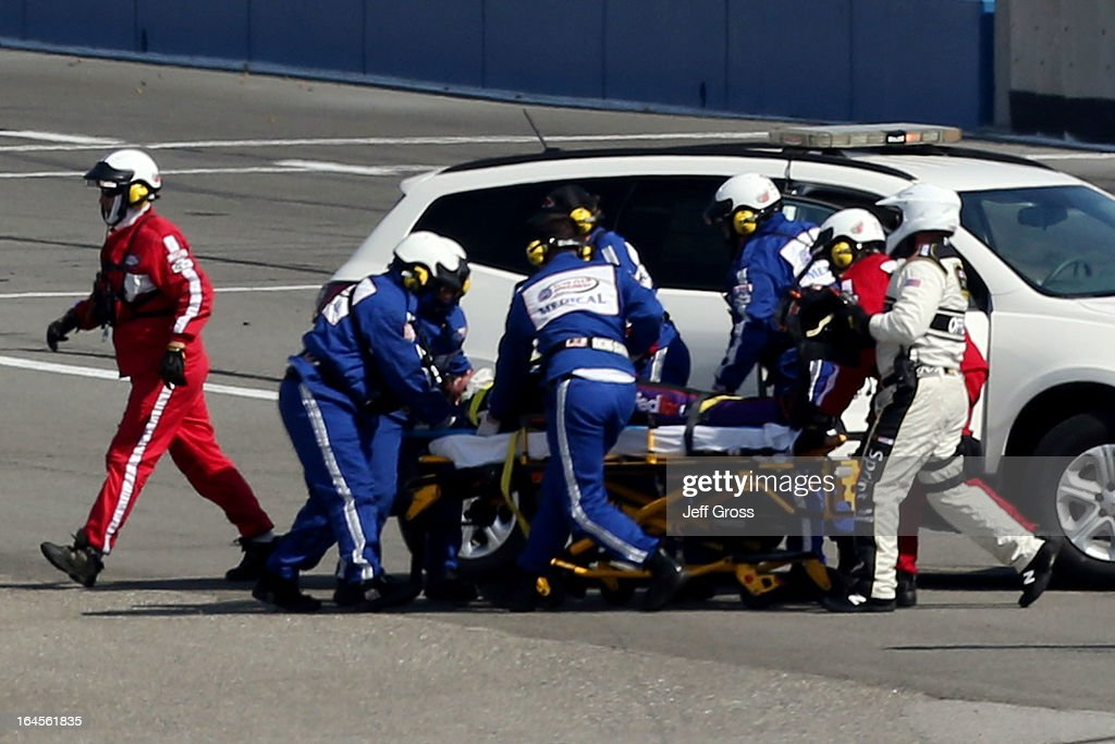 Safety workers attend to Denny Hamlin, driver of the #11 FedEx Express Toyota, after an incident with Joey Logano (not pictured), driver of the #22 AAA Southern California Ford, on the final lap during the NASCAR Sprint Cup Series Auto Club 400 at Auto Club Speedway on March 24, 2013 in Fontana, California.