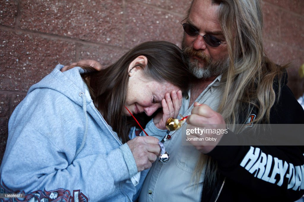 Safeway employee Sherrie Brown (R), is comforted by Leroy Wood, while participating in a ringing of the bells ceremony at a memorial for the six people that lost their lives in a deadly shooting last year in the parking lot of the La Toscana Village Safeway January 8, 2012 in Tucson, Arizona. Memorial services will be held throughout the day in Tucson to commemorate the one year anniversary of a shooting rampage that killed six people and wounded more than a dozen more including U.S. Rep. Gabrielle Giffords (D-AZ).