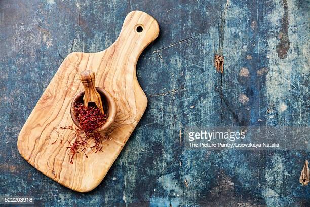 Saffron in olive wood bowl on blue wooden background