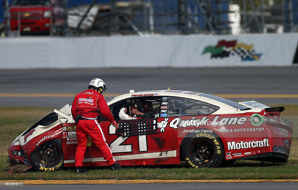 Safty workers assist Trevor Bayne out of the #21 Motorcraft/Quick Lane Tire & Auto Center Ford after an incident in the NASCAR Sprint Cup Series Budweiser Duel 1 at Daytona International Speedway on February 21, 2013 in Daytona Beach, Florida.
