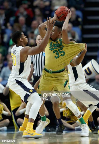 Sagaba Konate of the West Virginia Mountaineers tries to stop Bonzie Colson of the Notre Dame Fighting Irish during the second round of the 2017 NCAA...