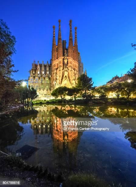 Sagrada Familia illuminated at dusk and reflected on lake in Barcelona, Catalonia, Spain