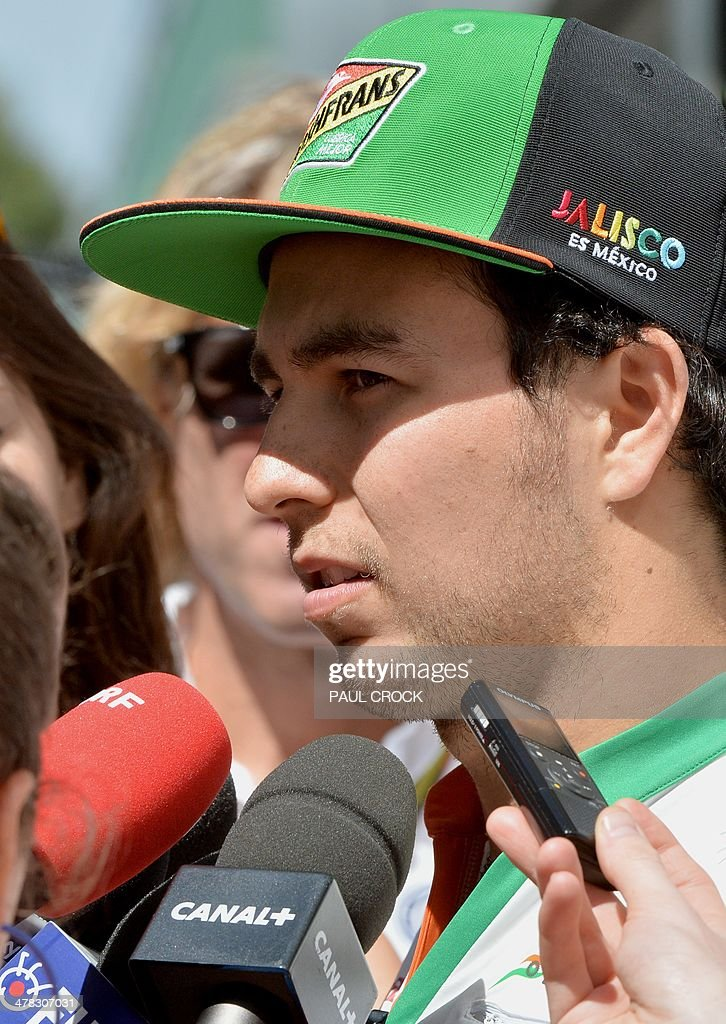 Sahara Force India driver Sercio Pérez of Mexico conducts an interview at the back of the pits ahead of the Formula One Australian Grand Prix in Melbourne on March 13, 2014. AFP PHOTO / Paul CROCK USE