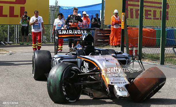 Sahara Force India F1 Team's German driver Nico Huelkenberg stands outside his damaged car after being forced to abandon the race during the...