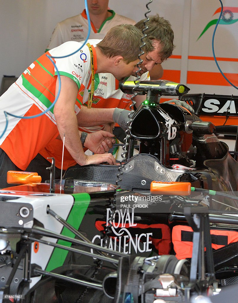 Sahara Force India mechanics prepare the car of Sercio Pérez of Mexico ahead of the Formula One Australian Grand Prix in Melbourne on March 13, 2014. AFP PHOTO / Paul CROCK USE