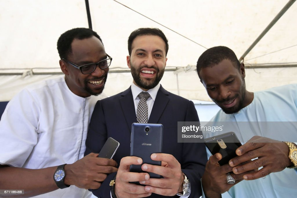 Sahir Berry, chief executive officer of AfriOne Ltd., center, poses for a photograph with an AfriOne Gravity Z1 smartphone during a launch event at the new AfriOne Ltd. manufacturing plant in Lagos, Nigeria, on Friday, April 21, 2017. The plant has the capacity to produce some 120,000 units per month. Photographer: George Osodi/Bloomberg via Getty Images