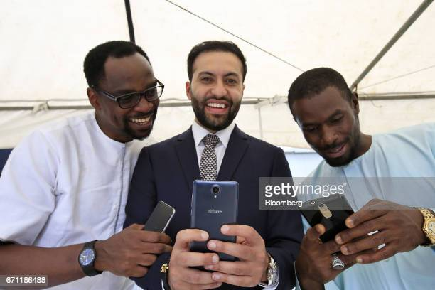 Sahir Berry chief executive officer of AfriOne Ltd center poses for a photograph with an AfriOne Gravity Z1 smartphone during a launch event at the...