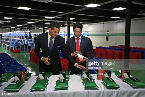 Sahir Berry chief executive officer of AfriOne Ltd left and Hemang Kapur director of AfriOne Ltd prepare a display of AfriOne Gravity Z1 smartphones...