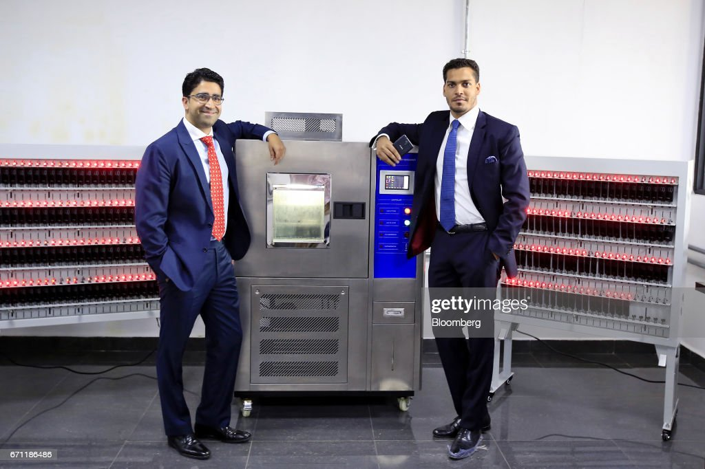 Sahir Berry, chief executive officer of AfriOne Ltd., right, and Hemang Kapur, director of AfriOne Ltd., pose for a photograph beside machinery during the launch event for the AfriOne Gravity Z1 smartphone at the new AfriOne Ltd. manufacturing plant in Lagos, Nigeria, on Friday, April 21, 2017. The plant has the capacity to produce some 120,000 units per month. Photographer: George Osodi/Bloomberg via Getty Images